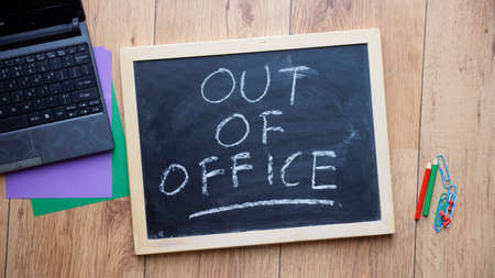 Out of office written on a chalkboard at the office photo