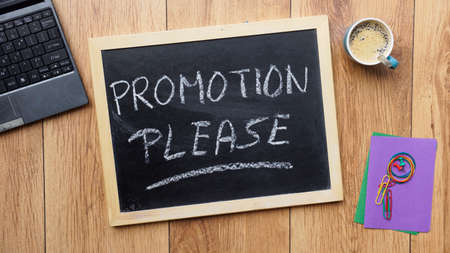 earn more: Promotion please written on a chalkboard at the office