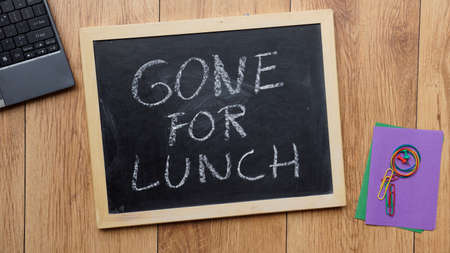 Gone for lunch written on a chalkboard at the office photo