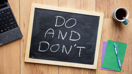 Do and dont written on a chalkboard at the office