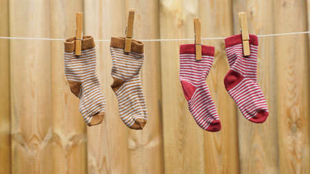 Two pair off child socks are hanging at the clotheslinein the sun photo
