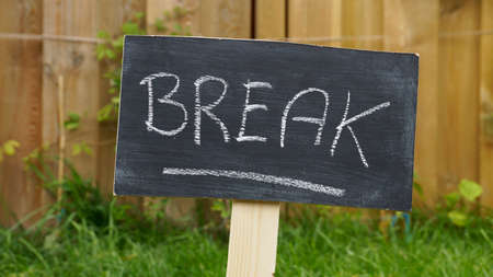take a breather: Break written on a chalkboard in the garden