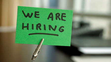 hiring: We are hiring written on a memo at the office Stock Photo