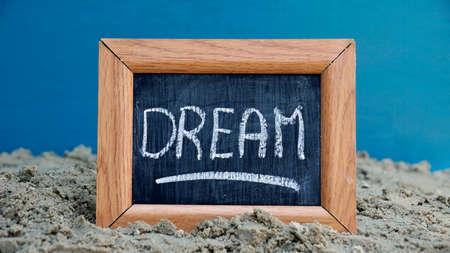 Dream written on a chalkboard at the beach photo