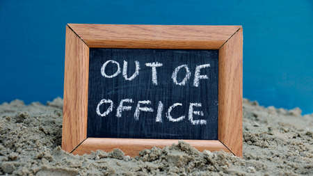 unoccupied: Out of office written on a chalkboard at the beach
