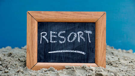 Resort written on a chalkboard at the beach photo