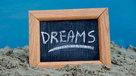 Dream written on a chalkboard at the beach photo
