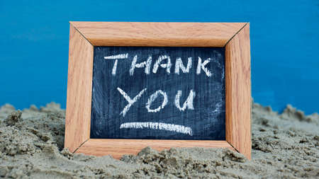 Thank you written on a chalkboard at the beach photo