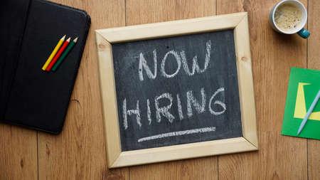 Now hiring written on a chalkboard at the office Standard-Bild