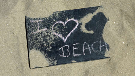 I love beach written on a chalkboard in the sand photo