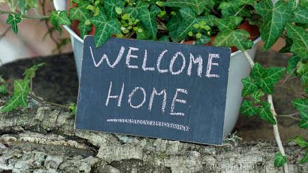 Welcome home written on a chalkboard in a garden