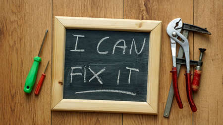 I can fix it written on a chalkboard with tools next to it Фото со стока