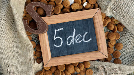 5 december: A chalkboard and a pile of Pepernoten, typical Dutch treat for Sinterklaas on 5 december Stock Photo