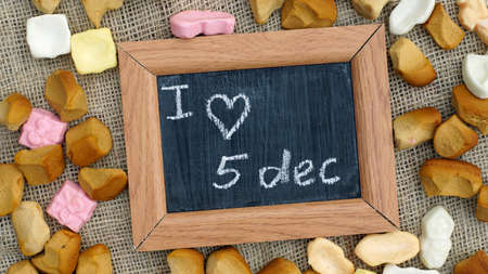 '5 december': A chalkboard and a pile of Pepernoten, typical Dutch treat for Sinterklaas on 5 december Stock Photo