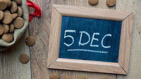 festiveness: Pile of Old Dutch Pepernoten and the word 5 DEC written, typical Dutch treat for Sinterklaas on 5 december