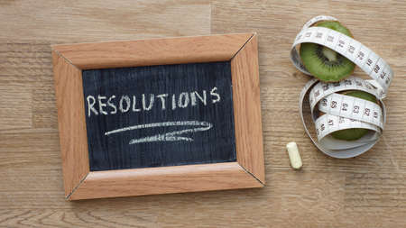 Resolutions written on a chalkboard next to a kiwi an inches