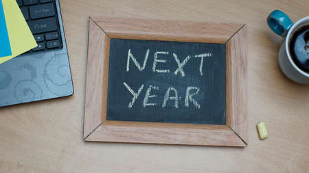 next year: Next year written on a chalkboard at the office Stock Photo