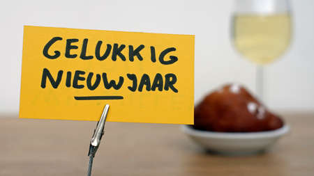 Happy new year written in Dutch, in the background a Dutch donut and drinks