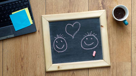 A heart and two smileys painted on a chalkboard at the office photo