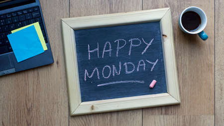 Happy monday written on a chalkboard at the office