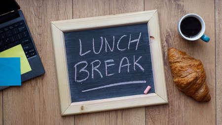Mittagspause auf einer Tafel geschrieben neben einem Frühstück im Büro Standard-Bild