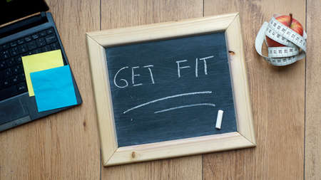 lunchbreak: Get fit written on a chalkboard at the office next to fruit