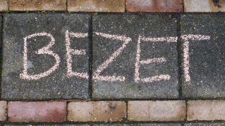 occupy: Occupy written in Dutch on the sidewalk for Kings day Stock Photo