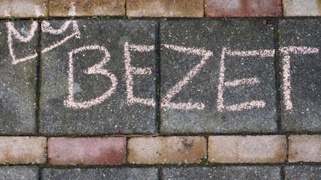Occupy written in Dutch with a crown on the sidewalk for Kings day