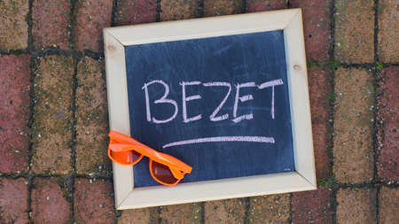 occupy: Occupy written in Dutch with sunglasses on the sidewalk for Kings day