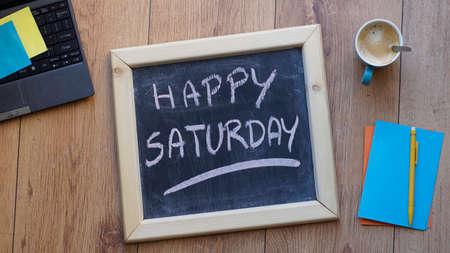 Happy saturday written on a chalkboard at the office Standard-Bild
