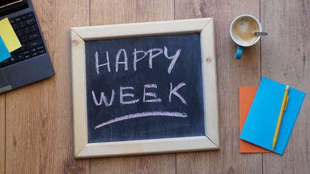 Happy week written on a chalkboard at the office