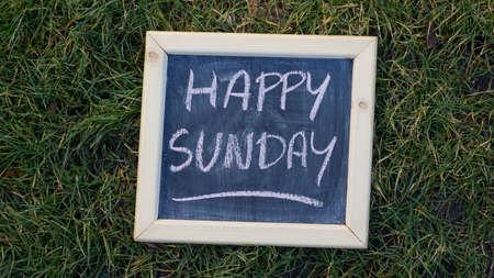 Happy sunday written on a chalkboard at the park Standard-Bild