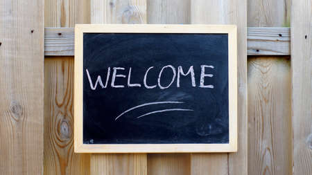 welcom: Welcome written on a chalkboard hanging outside at a wooden wall Stock Photo