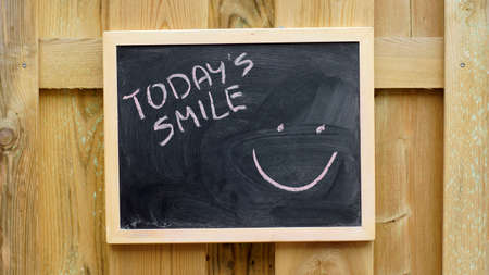 Todays smile written on a chalkboard hanging outside.