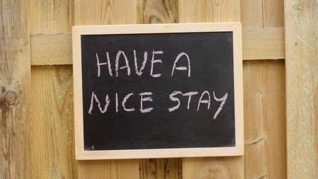 nice stay: Have a nice stay written at a chalkboard hanging at a wooden wall Stock Photo