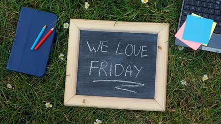 We love friday written on a chalkboard outside the office photo