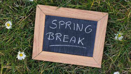 springbreak: Spring break written on a chalkboard in a park between grass and flowers