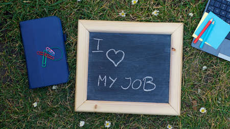 job vacancies: I love my job written on a chalkboard at the office in a park