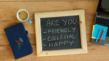 collegial: Are you friendly, collegial and happy skills written on a chalkboard at the office Stock Photo