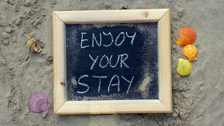 to stay: Enjoy your stay written on a chalkboard at the beach
