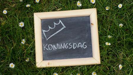 happening: Kingsday in Dutch written on a chalkboard in a park