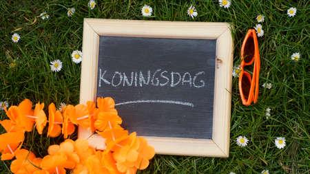 Kingsday v holandštině napsaný na tabuli v parku
