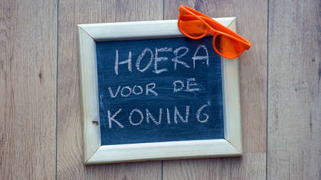 Kingsday in Dutch written on a chalkboard at a table