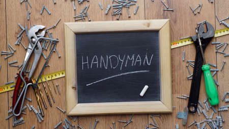 Handyman written on a chalkboard next to tools, screws and dowels