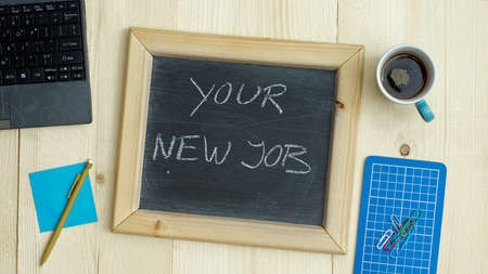 new recruit: Your new job written on a chalkboard at the office Stock Photo