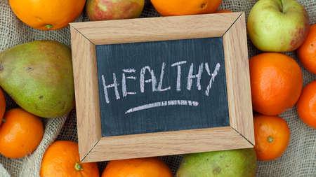 fruit: Healthy written on a chalkboard beween fruit
