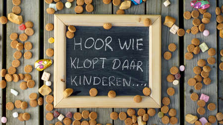 festiveness: The Santa-Claus song: hear who is knocking their children written in Dutch on a chalkboard between ginger nuts and candys for the Dutch Santa-Claus celebration of the 5th of Decembe