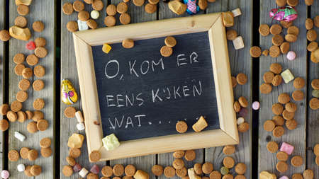 festiveness: The Santa-Claus song; come and look written in Dutch on a chalkboard between ginger nuts and candys for the Dutch Santa-Claus celebration of the 5th of Decembe