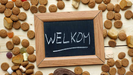 festiveness: Welcome in Dutch written on a chalkboard between ginger nuts and candys for the Dutch Santa-Claus celebration of the 5th of December