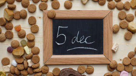 ginger nuts: 5th of December in Dutch written on a chalkboard between ginger nuts and candys for the Dutch Santa-Claus celebration of the 5th of December